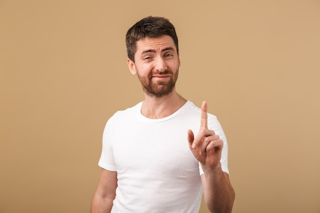 Portrait of a disappointed young man casually dressed showing stop gesture isolated over beige