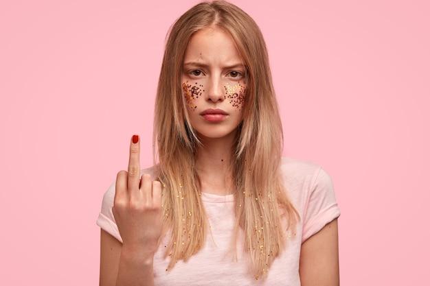 Ritratto di malcontento caucasica giovane femmina mostra il dito medio, ha scintillii sulle guance, è di basso spirito, discute con qualcuno, indossa una maglietta casual rosa chiaro in un tono con il muro