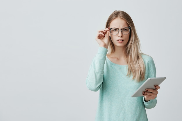 Portrait of discontent tired young beautiful businesswoman with blonde hair in spectacles stands against gray wall, works at new project on tablet, wants to have rest. negative emotions and feelings