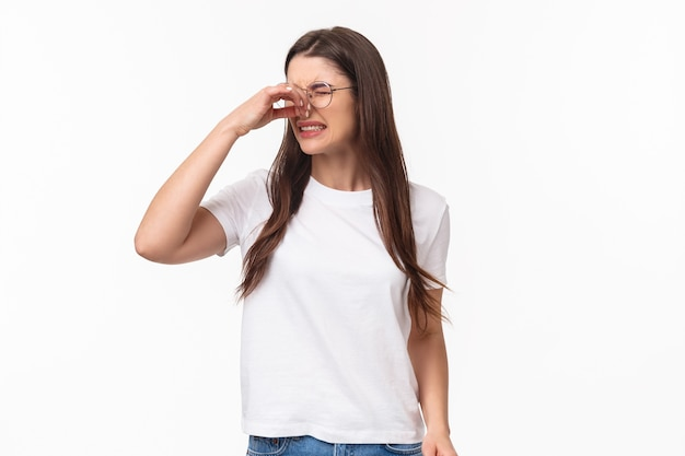 Ritratto di giovane bella ragazza disgustata e scontenta con gli occhiali, chiudere il naso