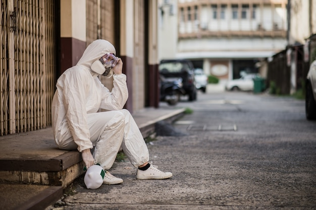 公共の除染を行うppeスーツ、手袋、マスク、フェイスシールドの肖像画消毒スペシャリストの男性、消毒中に疲れを感じて座ってcovid-19を除去する