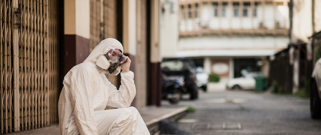 Portrait disinfection specialist man in ppe suit, gloves, mask and face shield performing public decontamination, sitting with feel tired during disinfectant to remove covid-19