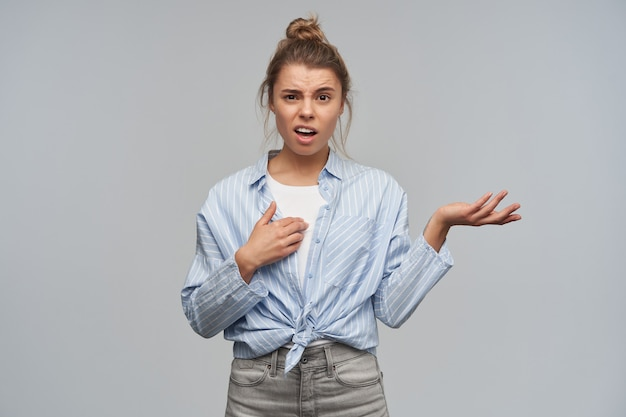 Portrait of displeased, adult girl with blond hair gathered in bun. wearing striped knotted shirt. pointing at herself, frowns and shrug her hand. looking at the camera, isolated over grey wall