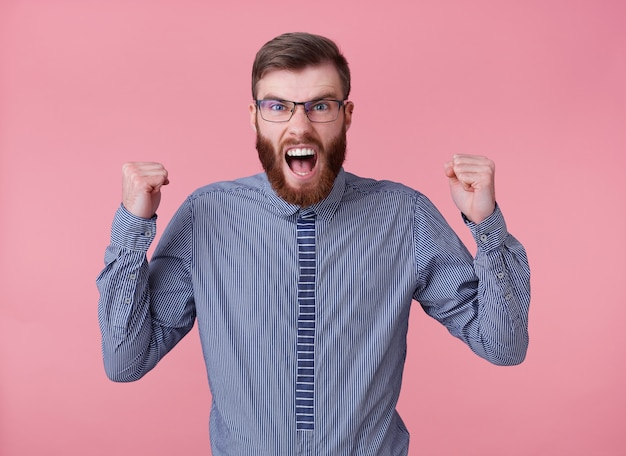 Portrait of displeased angry young handsome red bearded man with glasses and a striped shirt, stands over pink background, screaming with fists raised.