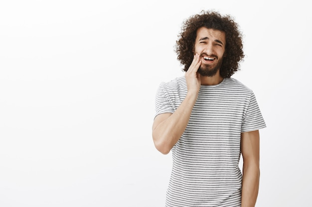 Portrait of displeased bothered handsome eastern male student with afro hairstyle in striped t-shirt, touching beard and grimacing from dislike, feeling need to shave stubble