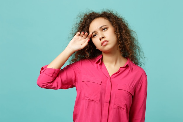 Ritratto di una ragazza africana che piange dispiaciuta in abiti casual rosa che guardano da parte isolato su sfondo blu turchese della parete in studio. persone sincere emozioni, concetto di stile di vita. mock up copia spazio.