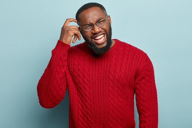 Portrait of displeased dark skinned man scratches head, has dissatisfied expression, frowns face and shows white teeth, wears red jumper, isolated over blue wall. negative feelings concept