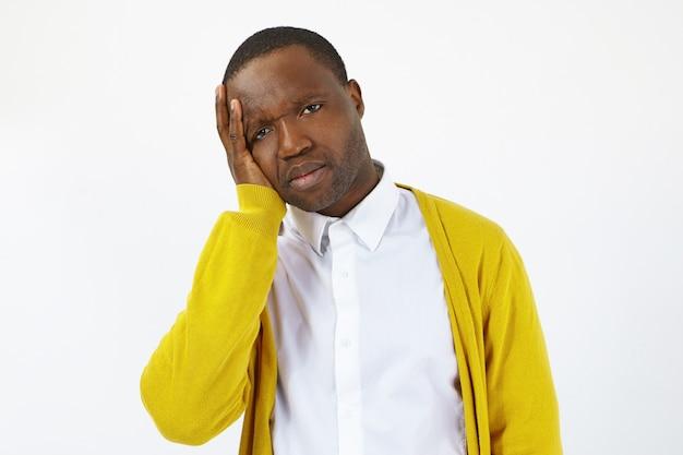 Ritratto di uomo africano frustrato dispiaciuto che si sente male e malato, toccando la testa a causa di emicrania o mal di denti dopo una giornata stressante al lavoro, in posa isolato su sfondo muro bianco studio
