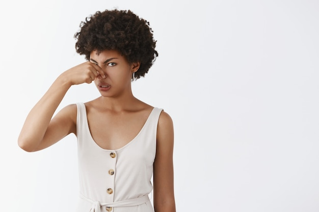 Portrait of displeased intense disappointed african american funny woman with afro hairstyle covering nose with fingers frowning from dislike