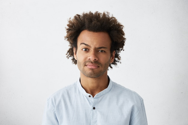 Portrait of displeased mixed race attractive man with dark narrow eyes and curly thick hair