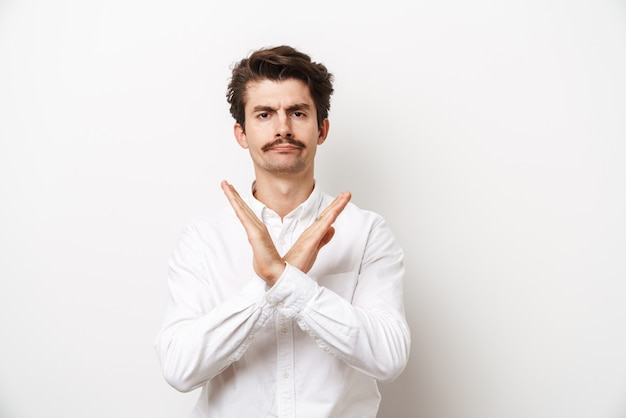 Portrait of displeased mustached man wearing shirt looking at front with hands crossed isolated on white