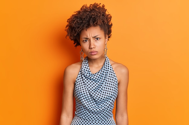 Portrait of displeased offended dark skinned woman looks with disappointed expression