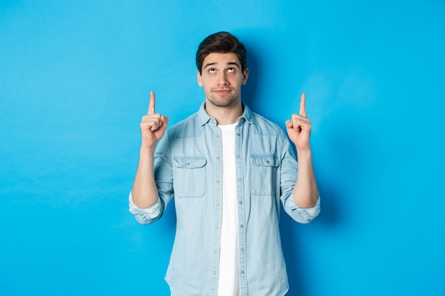 Portrait of displeased and skeptical male model pointing fingers up, looking at something unpleasant, standing against blue background.