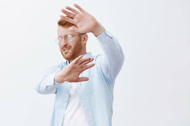 Ritratto del famoso imprenditore maschio scontento, turbato e preoccupato con i capelli rossi, voltandosi, coprendosi il viso con i palmi sollevati, cercando di nascondersi dai paparazzi sul muro grigio