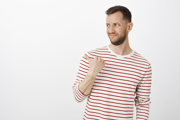 Portrait of displeased unimpressed guy in casual outfit, frowning and pointing backwards or left, expressing dislike and doubt, sharing opinion about bad play to friend