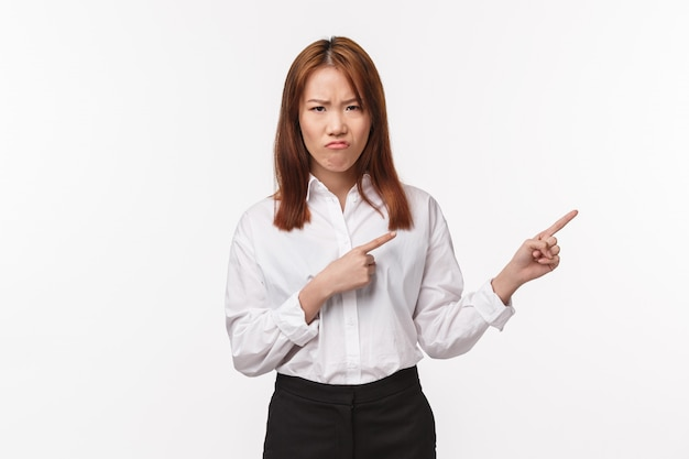 Portrait of displeased and unsatisfied asian young woman in shirt, grimacing and frowning with disgust and disappointment, pointing right at something upsetting and bothering, white wall