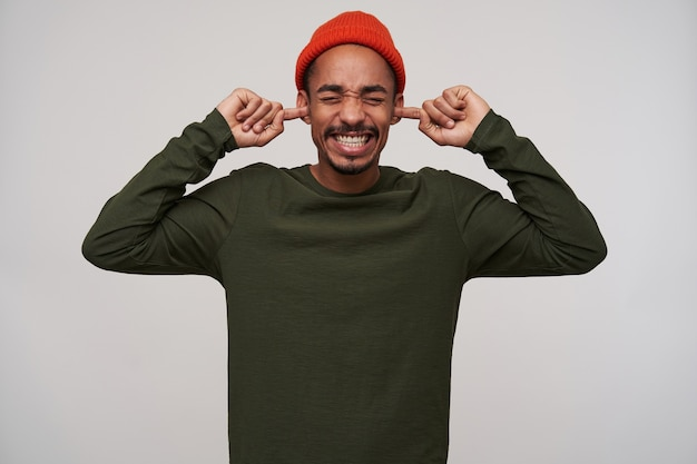 Portrait of displeased young bearded dark skinned guy keeping eyes closed while coning his ears with index fingers because of loud sounds, isolated on white
