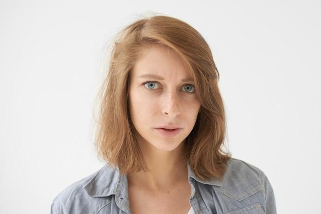 Ritratto di giovane femmina caucasica dispiaciuta con le lentiggini e gli occhi azzurri che aggrottano le sopracciglia avendo un'espressione facciale rigorosa e cupa. emozioni umane, reazione, sentimenti, percezione della vita e atteggiamento