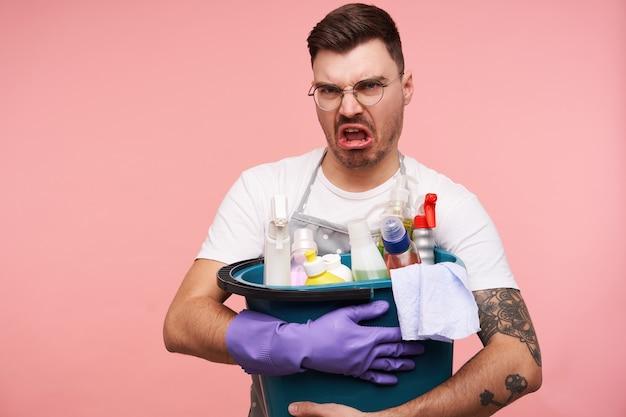 Ritratto di giovane uomo dai capelli scuri scontento in occhiali non vuole fare la pulizia