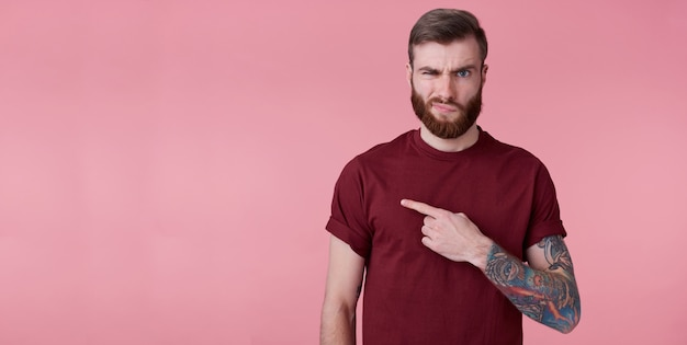 Portrait of displeased young handsome red bearded man in red shirt, wants to draw your attention to copy space on the left side, frowns face in displeasure, stands over pink background.