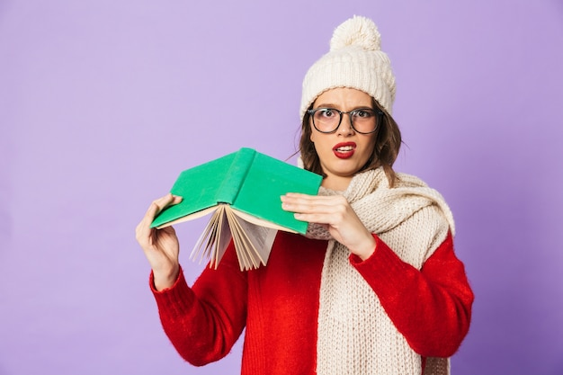 Portrait of a displeased young woman wearing winter hat isolated over purple wall reading book.
