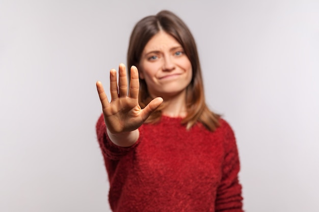 Portrait of dissatisfied girl in shaggy sweater stretching out hand, warning with stop gesture