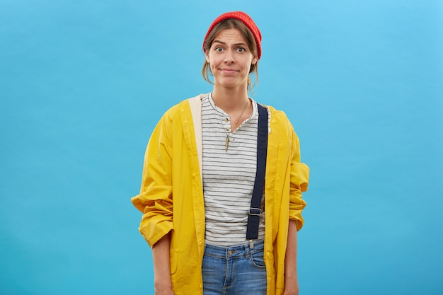 Portrait of dissatisfied woman wearing red hat, yellow raincoat and overalls frowning her face having bad mood as her husband didn't take her on lake to go fishing. facial expressions and emotions