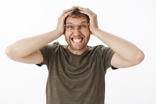 Ritratto di giovane impiegato maschio infastidito afflitto in maglietta verde e occhiali che stringono i denti che tengono le mani sulla testa in posa senza speranza avente una giornata schifosa