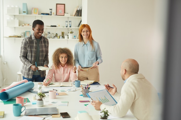Portrait of diverse business team collaborating on business project during meeting in modern white office and smiling cheerfully