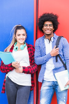Portrait of diverse female and male student smiling to camera against wall
