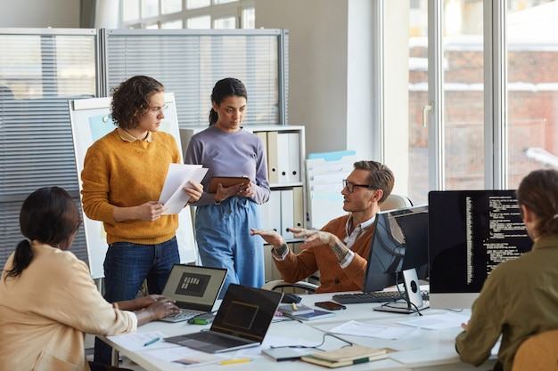 Portrait of diverse software development team collaborating on project in modern office, focus on lead engineer instructing colleagues, copy space