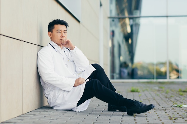 Portrait doctor asian man tired after work sitting on the floor near the clinic disappointed with the result
