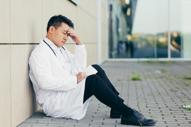 クリニック近くの床に座って仕事をした後疲れたポートレートドクターアジア人男性は結果に失望した