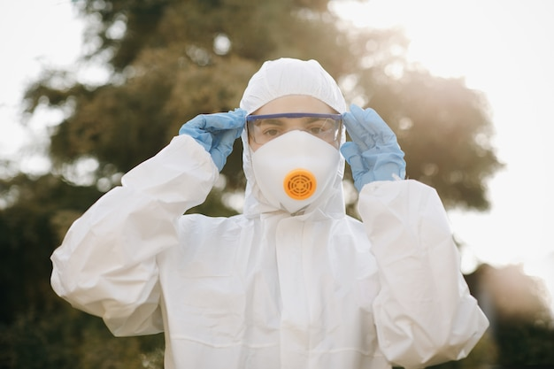 Portrait of doctor epidemiologist fighting with coronavirus covid-19. protection mers by virologist. white medical suit with mask, gloves, glasses. face of global crisis during epidemic.