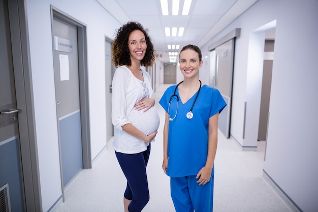 Portrait of doctor and pregnant womans standing in corridor
