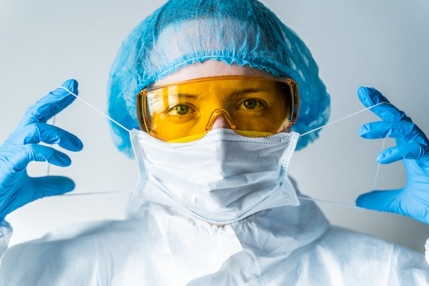 Portrait of a doctor putting on a mask and blue uniform. isolated on white background. 2019-ncov pandemic, novel chinese coronavirus, wuhan coronavirus concept.