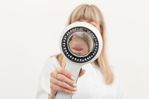 Portrait of a doctor trichologist dermatologist looking at a dermatoscope