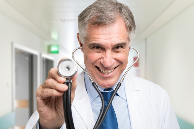 Portrait of a doctor using his stethoscope. isolated on white background