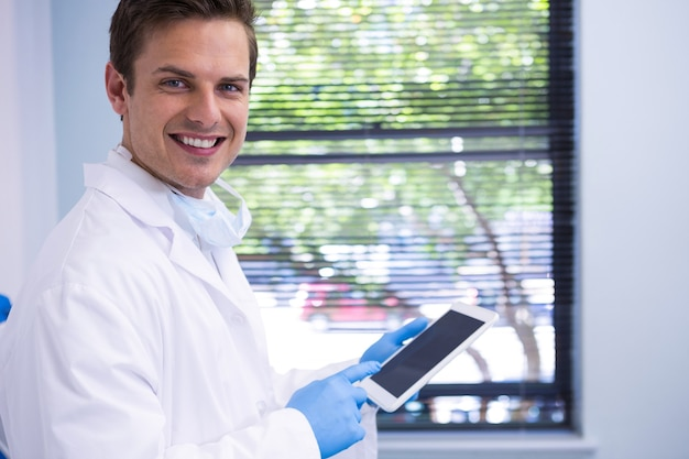Portrait of doctor using tablet while standing against wall