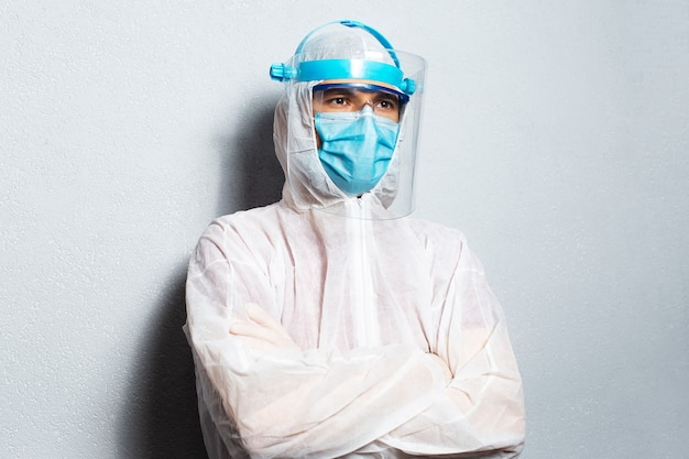 Portrait of a doctor wearing ppe suit against coronavirus and covid-19, on the background of white wall.
