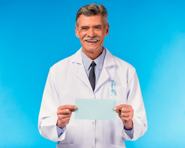 Portrait of a doctor with a blue ribbon on blue wall.