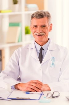 Portrait of doctor with blue ribbon sitting in his office.