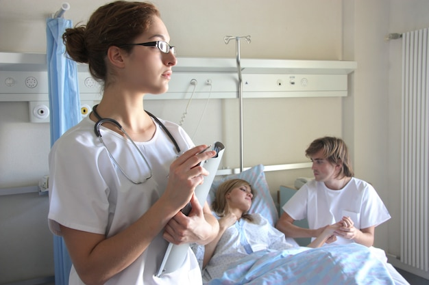 Portrait of a doctor with a her coworkers talking with a patient in the background