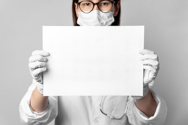 Portrait of doctor with surgical mask holding a sign