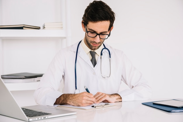 Portrait of a doctor writing on clipboard in clinic
