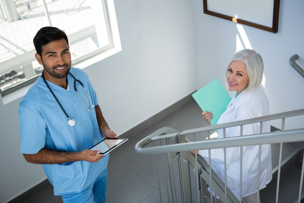 Portrait of doctors smiling while standing on staircase