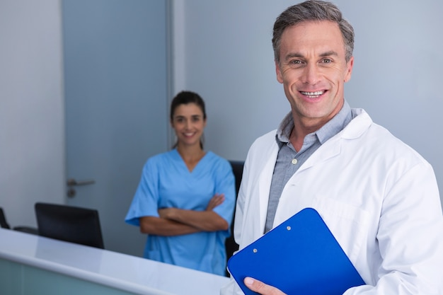 Portrait of doctors standing against wall