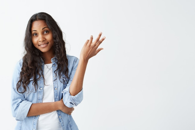 Ritratto di giovane donna afroamericana dubbiosa che osserva con la perplessità isolata sulla parete bianca. piacevole donna dalla pelle scura vestita in camicia di jeans che ha confuso e incerto