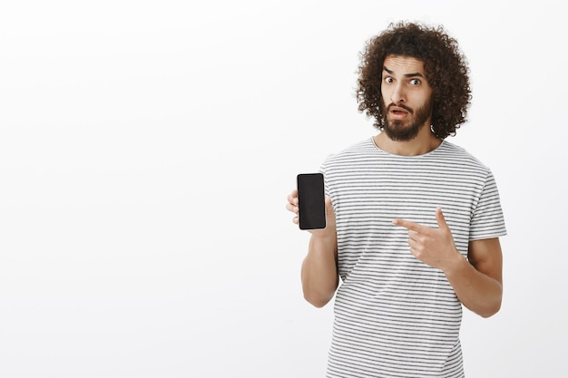 Portrait of doubtful disbelieving attractive male with curly hair, holding smartphone and pointing with index finger at device