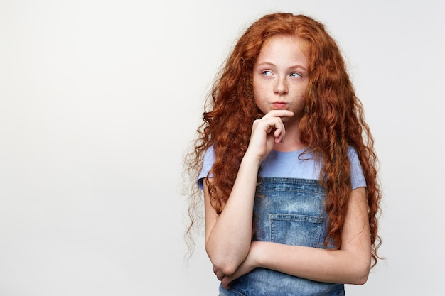 Portrait of doubting cute freckles little girl with ginger hair, thinking about something, touches chin, looks away over white background with copy space on the left side.